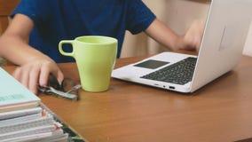 男孩少年倾倒了在膝上型计算机之上的茶 做家庭作业,在网上学会,4k特写镜头, 股票录像
