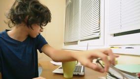男孩少年倾倒了在膝上型计算机之上的茶 做家庭作业,在网上学会,4k特写镜头, 影视素材