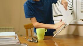 男孩少年倾倒了在膝上型计算机之上的茶 做家庭作业,在网上学会,4k特写镜头, 股票视频
