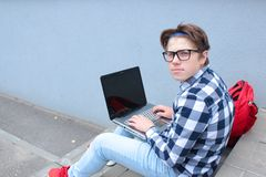 男孩少年男小学生或学生坐台阶,工作在计算机,佩带的玻璃,在衬衣,微笑,红色b 免版税库存照片