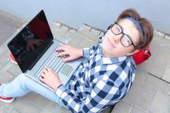 男孩少年男小学生或学生坐台阶,工作在计算机,佩带的玻璃,在衬衣,微笑,红色b 免版税库存图片