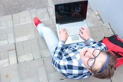 男孩少年男小学生或学生坐台阶,工作在计算机,佩带的玻璃,在衬衣,微笑,红色b 库存照片