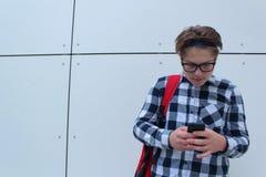 男孩少年男小学生或学生衬衣的,微笑与玻璃,红色背包 库存照片