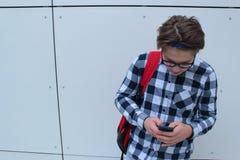 男孩少年男小学生或学生衬衣的,微笑与玻璃,红色背包 图库摄影