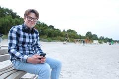 男孩少年男小学生或学生衬衣的,微笑在玻璃,听到音乐在电话 库存照片