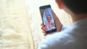 男孩少年举行与一名妇女的录影闲谈智能手机的 股票录像