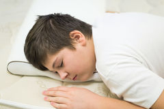男孩少年睡觉面孔下来在解剖枕头 免版税库存图片