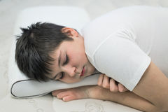 男孩少年睡觉面孔下来在解剖枕头 免版税库存照片