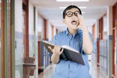 男孩尖叫与在他的手上的书 图库摄影