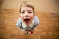 男孩尖叫的一点 开放男孩的嘴 库存图片
