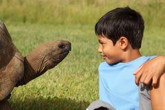 男孩巨型草龟 库存图片
