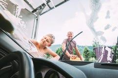 男孩帮助他的有汽车洗涤物的父亲 图库摄影
