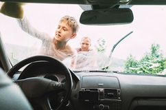 男孩帮助他的父亲洗涤汽车 免版税库存图片