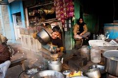 男孩帮助烹调印地安茶masala用牛奶和香料 免版税库存图片