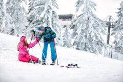 男孩帮助给女孩从与滑雪的雪起来 库存图片