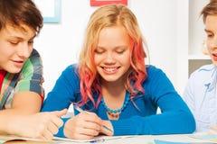 男孩帮助逗人喜爱的白肤金发的青少年的女孩做家庭作业 免版税库存照片