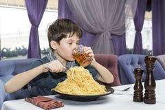 男孩开胃吃大意大利意粉 免版税图库摄影