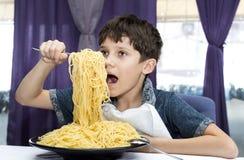 男孩开胃吃大意大利意粉 库存照片