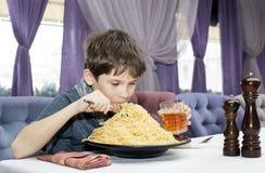 男孩开胃吃大意大利意粉 免版税库存照片