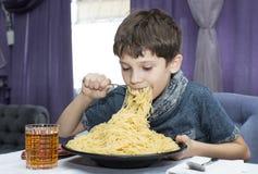 男孩开胃吃大意大利意粉 库存图片