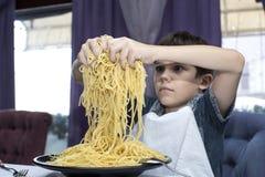 男孩开胃吃大意大利意粉 免版税库存图片