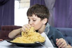 男孩开胃吃大意大利意粉 图库摄影