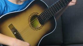 男孩弹吉他坐长沙发,手特写镜头 学会的概念弹奏一个乐器 股票录像