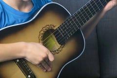 男孩弹吉他坐长沙发,手特写镜头 学会的概念弹奏一个乐器 免版税库存图片