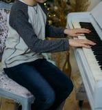 男孩弹钢琴 他坐椅子在钢琴附近 实践弹奏仪器 按钢琴键 免版税库存照片