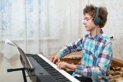 男孩弹钢琴 免版税库存照片