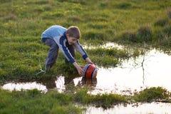 男孩得到与水坑的球在草 库存照片