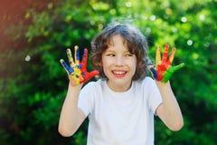 年轻男孩微笑和显示他五颜六色的手 库存照片