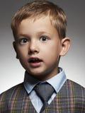 男孩微笑的一点 衣服和领带的时髦的孩子 免版税库存照片