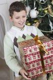 男孩惊奇与一件大圣诞节礼物 库存照片