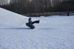 男孩愉快地滑在雪管的雪小山下 库存照片