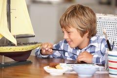 男孩愉快的做的模型船年轻人 免版税库存照片