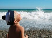男孩愉快的海边坐微笑 库存照片