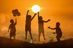 男孩愉快的跳跃的接触剪影太阳 免版税图库摄影