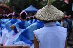 男孩戴的华丽椰子帽子,他们在街道上跳舞 免版税库存图片