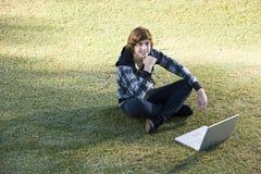男孩户外草膝上型计算机少年使用 图库摄影