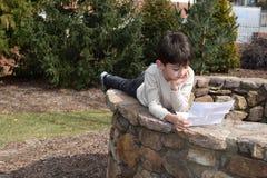 男孩户外读书信件 免版税库存图片