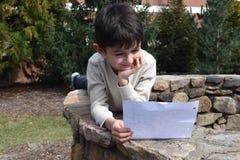 男孩户外读书信件 库存照片