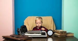 男孩打字关于葡萄酒打字机的专题报告 在书面报告的一点摄影记者工作在办公桌 库存照片