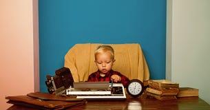 男孩打字关于葡萄酒打字机的专题报告 在书面报告的一点摄影记者工作在办公桌 免版税库存图片