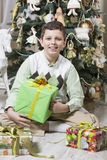 男孩打开圣诞节礼物 免版税库存图片