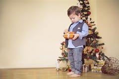 男孩打开当前在圣诞树前面 免版税库存照片