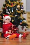 男孩打开礼物在圣诞树下 免版税图库摄影