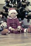 男孩打开礼物在圣诞树下 库存图片