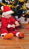 男孩打开礼物在圣诞树下 免版税库存图片