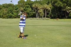 男孩打高尔夫球的年轻人 图库摄影